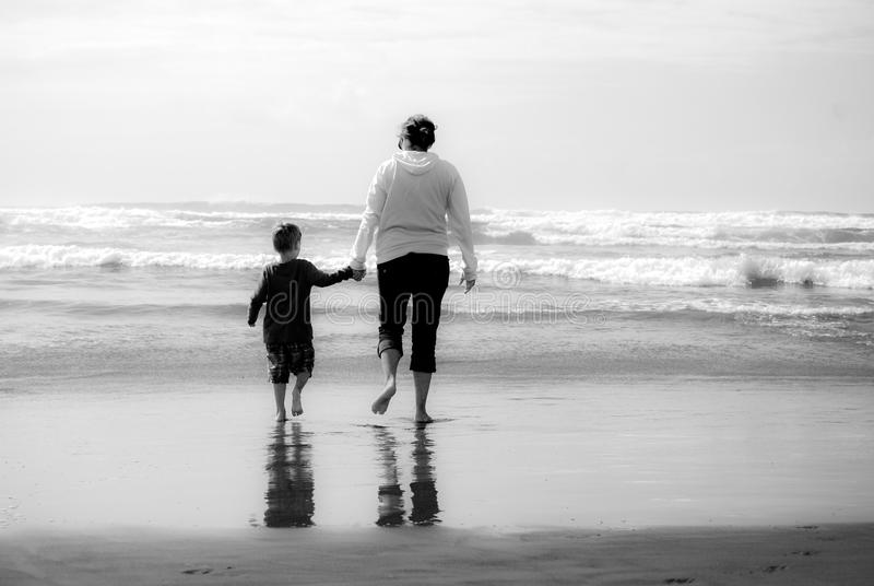 Moder- och barnhållhänder på stranden arkivfoto