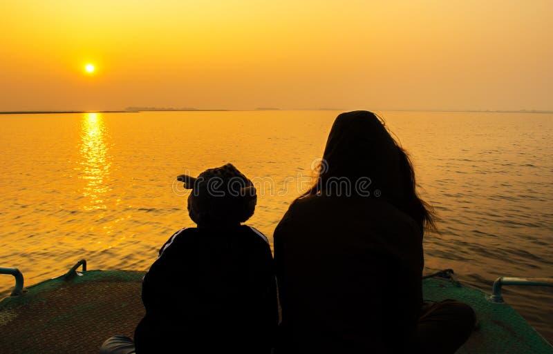 Moder- och barnkontur i solnedgången royaltyfria bilder