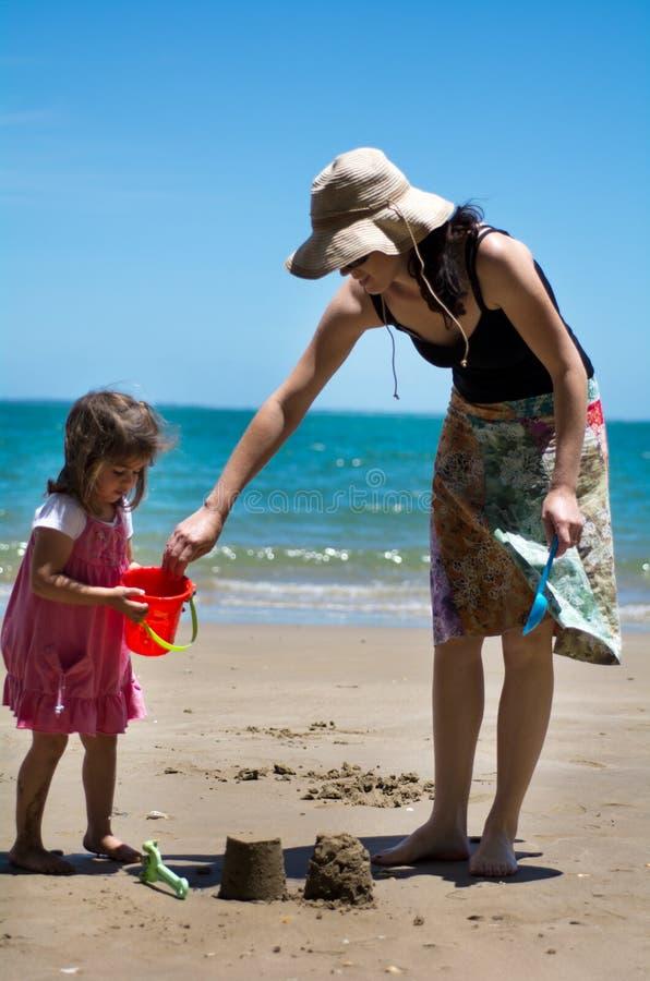 Moder- och barnlekar på stranden arkivfoto