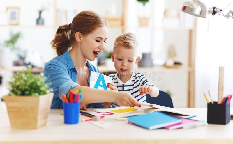 Moder- och barnson som gör läxahandstil och hemma läser arkivfoton