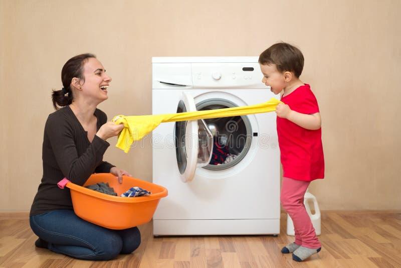 Moder och daugher som spelar nära tvagningmaskinen royaltyfria bilder
