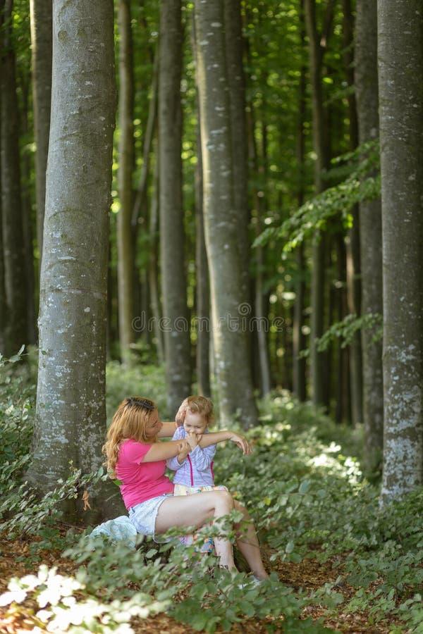 Moder- och dotterögonblick inom skogen Smilling och ha en bra tid r royaltyfri fotografi