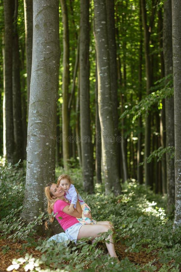 Moder- och dotterögonblick inom skogen Smilling och ha en bra tid r arkivbild