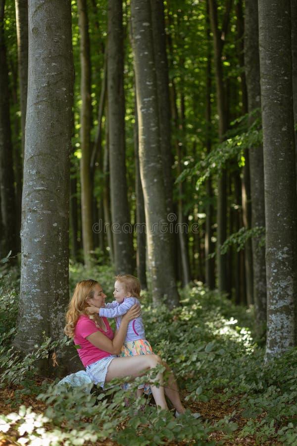 Moder- och dotterögonblick inom skogen Smilling och ha en bra tid r royaltyfri foto