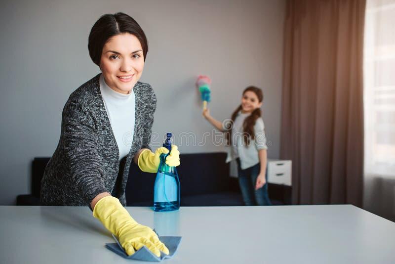 Moder och dotter för härlig brunett som caucasian tillsammans gör ren i rum Gladlynt tvagningskrivbord och håll för ung kvinna arkivbild