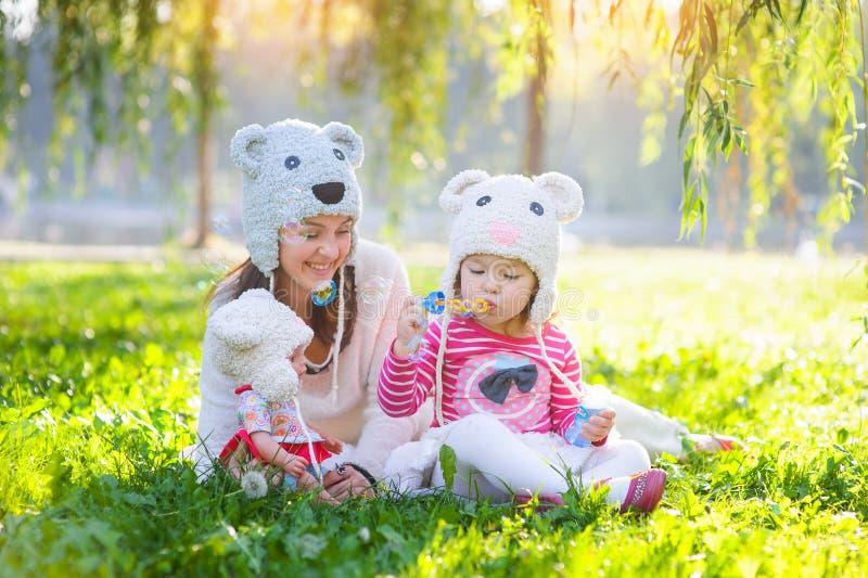 Moder och dotter i en parkera som bär en rät maskahatt royaltyfri foto