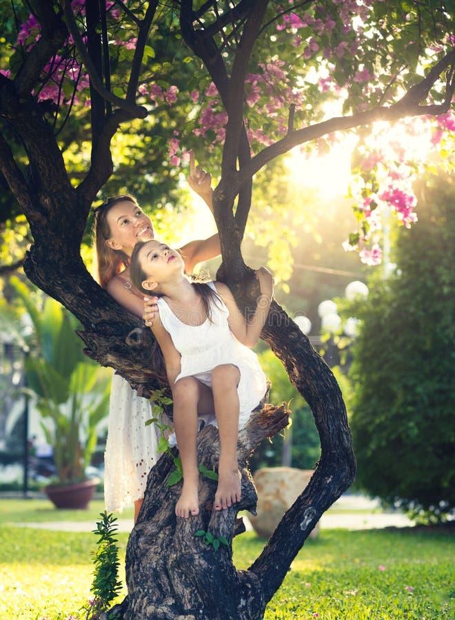 Moder och dotter i en sagolik trädgård royaltyfri foto
