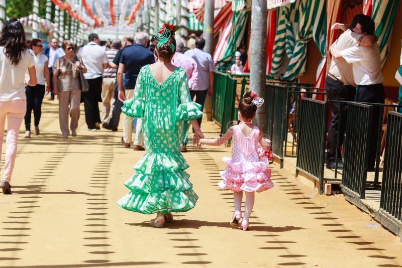Moder och dotter i traditionell klänning som tillsammans med går Casetas på den Seville mässan royaltyfri bild