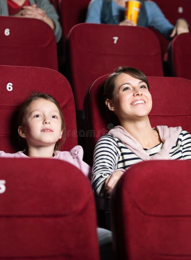 Moder och dotter på bion royaltyfria bilder