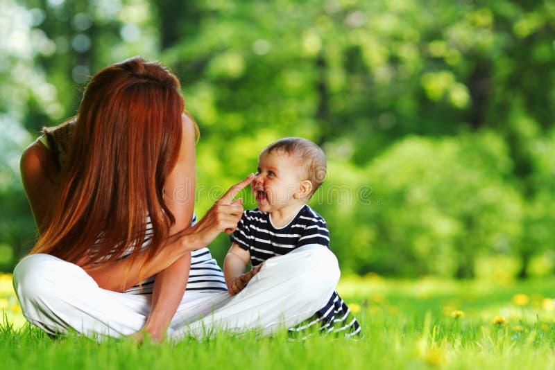 Moder och dotter på det gröna gräset arkivbilder