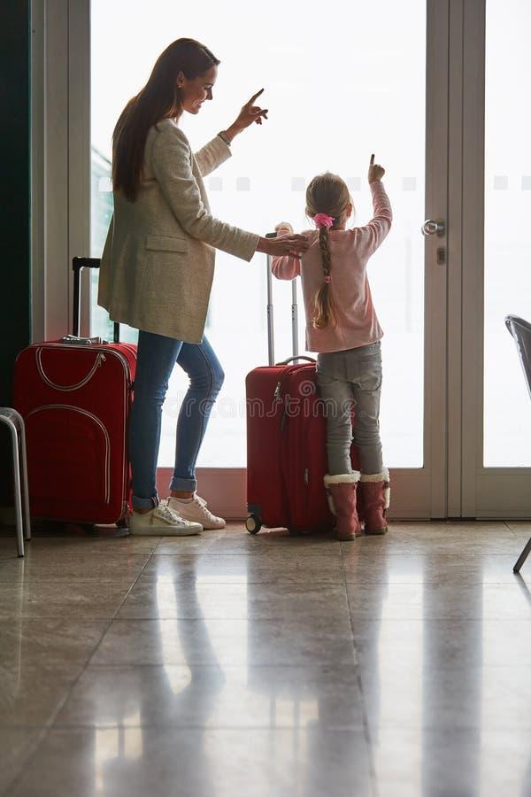 Moder och dotter på fönstret i flygplatsterminalen royaltyfria bilder