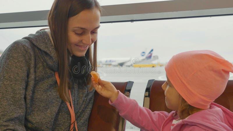 Moder och dotter på flygplatsen Liten flickamandarin på den väntande korridoren arkivfoton