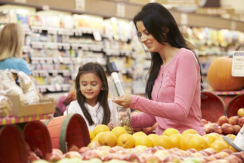Moder och dotter på frukträknaren i supermarket royaltyfria bilder