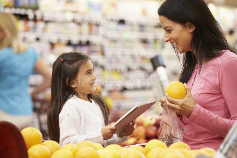 Moder och dotter på frukträknaren i supermarket med listan arkivfoto