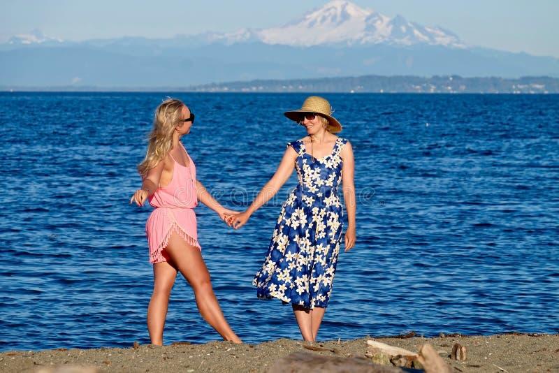 Moder och dotter på stranden vid havet fotografering för bildbyråer
