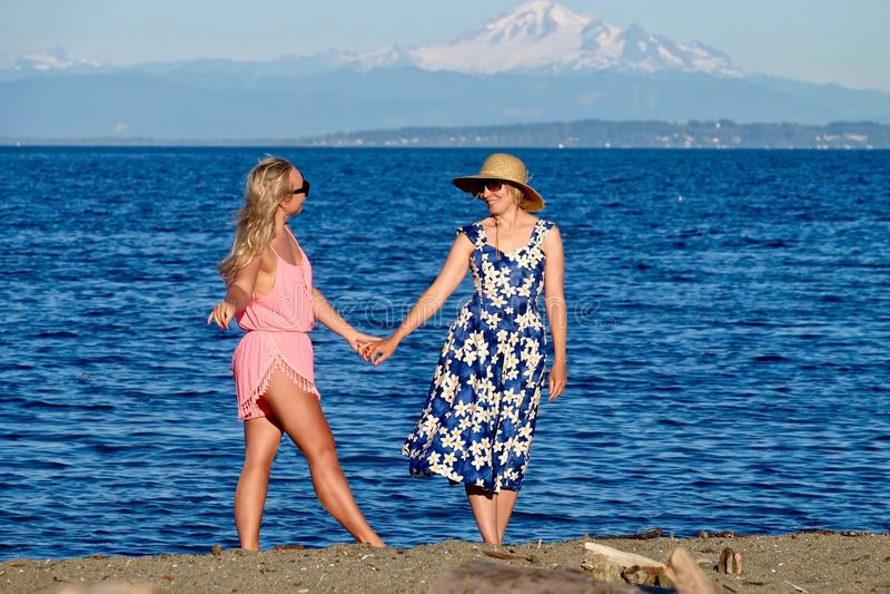 Moder och dotter på stranden vid havet royaltyfri foto