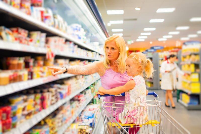 Moder och dotter på supermarket royaltyfri bild