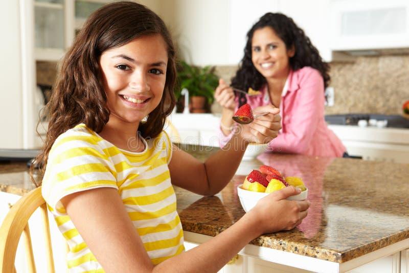 Moder och dotter som äter sädesslag och frukt arkivfoton