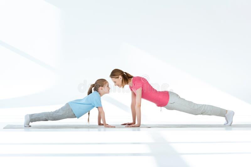Moder och dotter som övar på yogamats royaltyfri foto