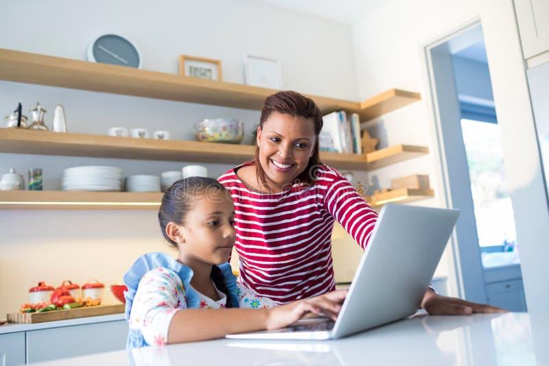 Moder och dotter som använder bärbara datorn i kökworktop royaltyfri bild