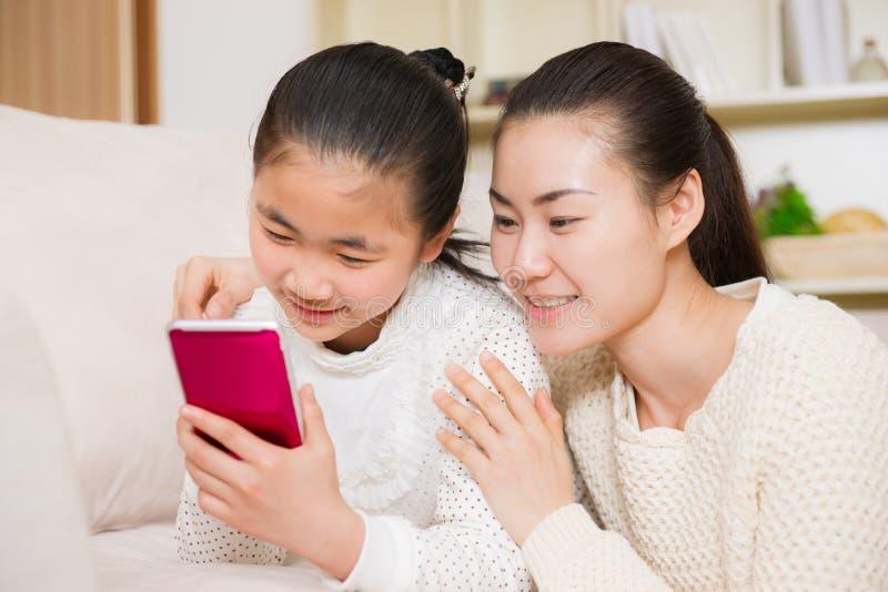Moder och dotter som använder den smarta telefonen royaltyfri bild