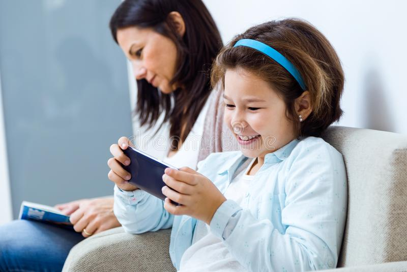 Moder och dotter som använder mobiltelefonen i det väntande rummet av doktorn royaltyfri foto