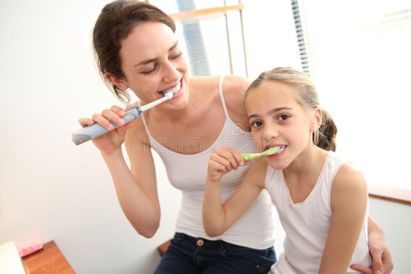 Moder och dotter som använder tandborstar royaltyfria foton
