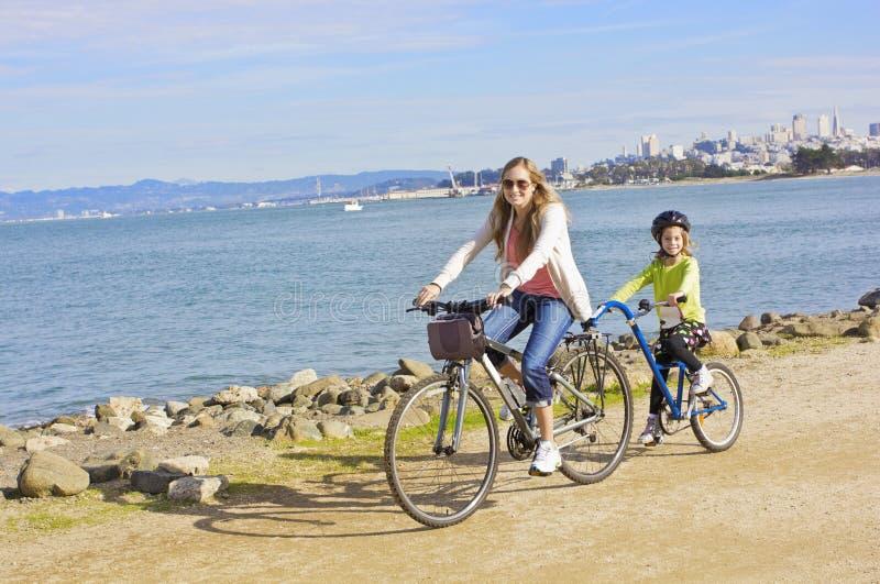 Moder och dotter som cyklar längs stranden i San Francisco royaltyfri fotografi