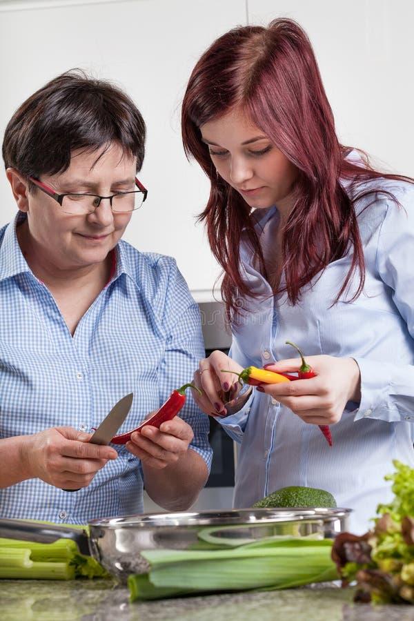 Moder och dotter som förbereder mat royaltyfri foto