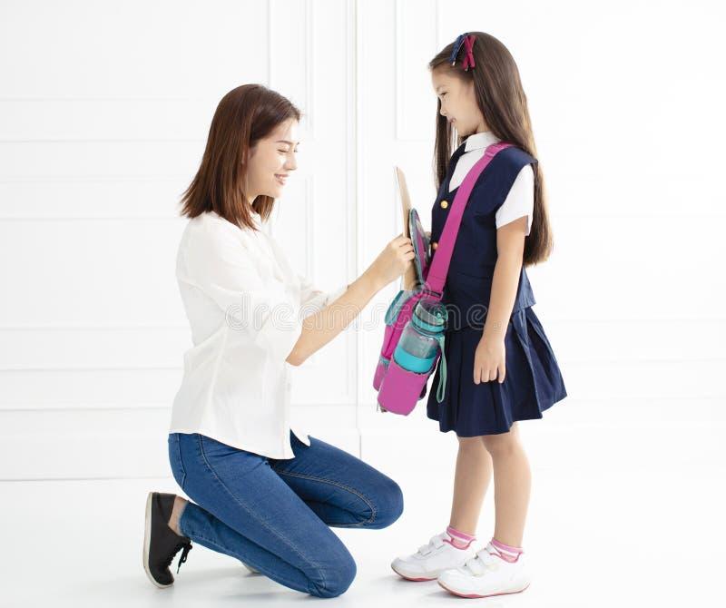 Moder och dotter som förbereder ryggsäcken för skola arkivbild