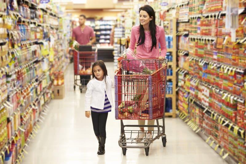 Moder och dotter som går ner livsmedelsbutikgången i supermarket fotografering för bildbyråer