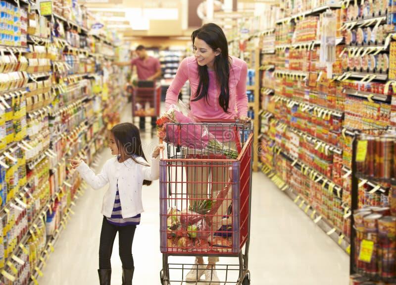 Moder och dotter som går ner livsmedelsbutikgången i supermarket arkivbild