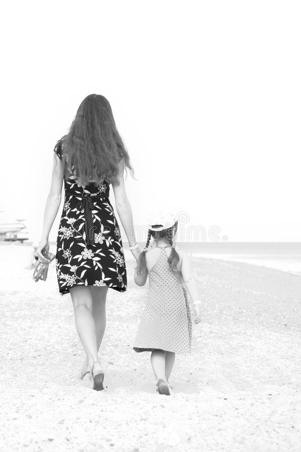 Moder och dotter som går på stranden. Svartvitt. royaltyfria bilder