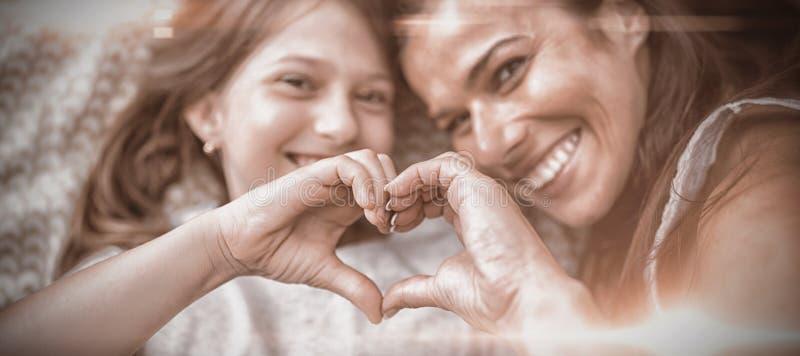 Moder och dotter som gör hjärtaform med händer, medan ligga på säng royaltyfri foto