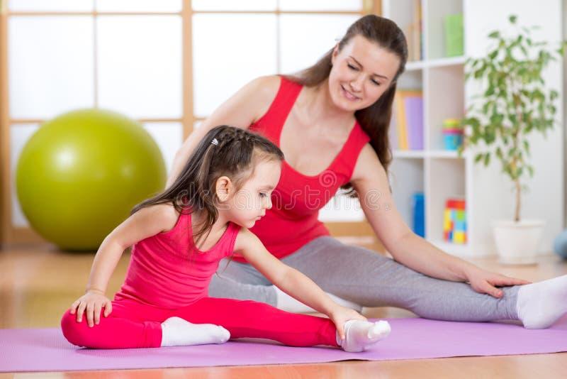 Moder och dotter som gör konditionövningar på mattt hemmastatt fotografering för bildbyråer