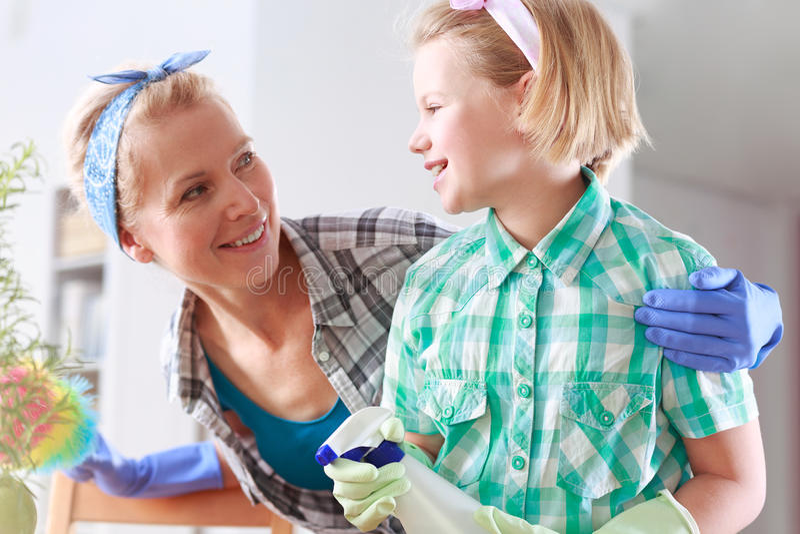 Moder och dotter som gör ren deras hus fotografering för bildbyråer