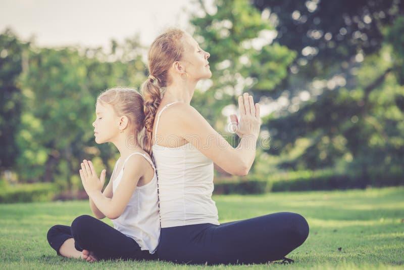 Moder och dotter som gör yogaövningar på gräs i parkera arkivfoton
