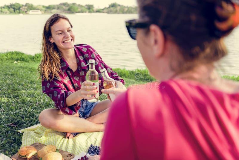 Moder och dotter som har en picknick i parkera arkivfoto