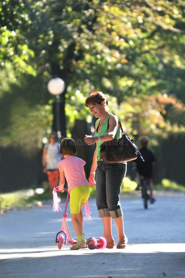 Moder och dotter som har gyckel i park arkivfoto