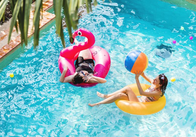 Moder och dotter som har gyckel i simbassängen arkivfoton