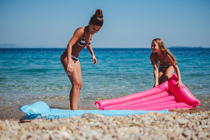 Moder och dotter som har gyckel med att sväva säng på stranden royaltyfria bilder