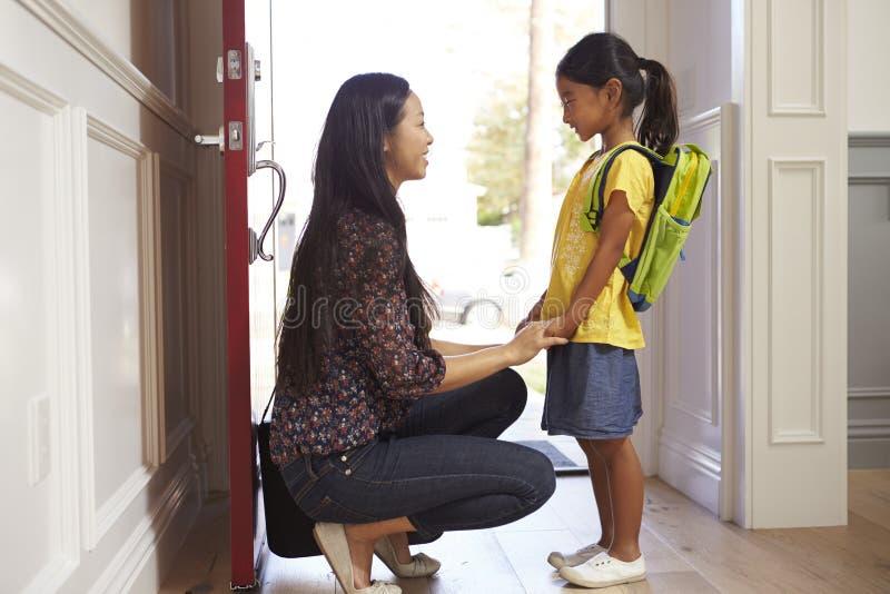 Moder och dotter som hem lämnar för skola arkivfoto