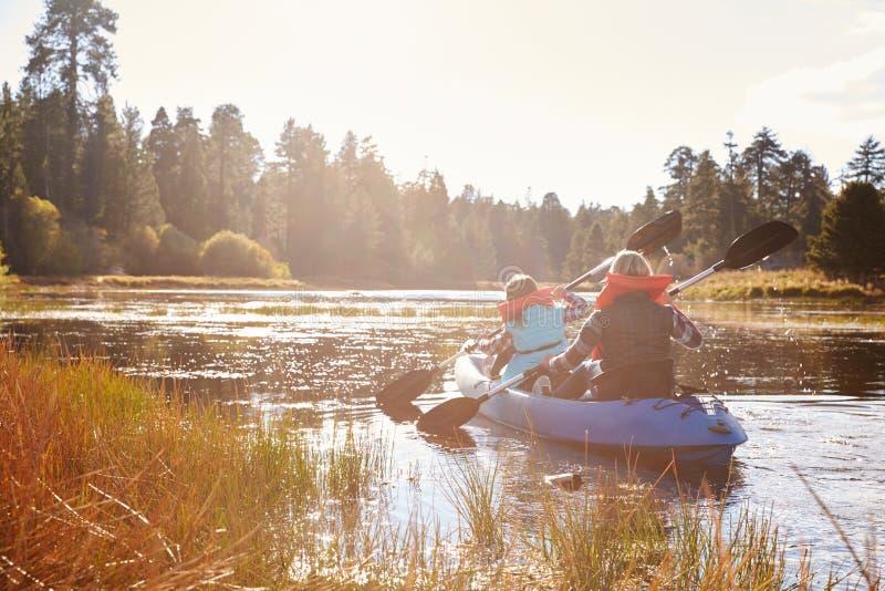 Moder och dotter som kayaking på sjön, baksidasikt royaltyfria bilder