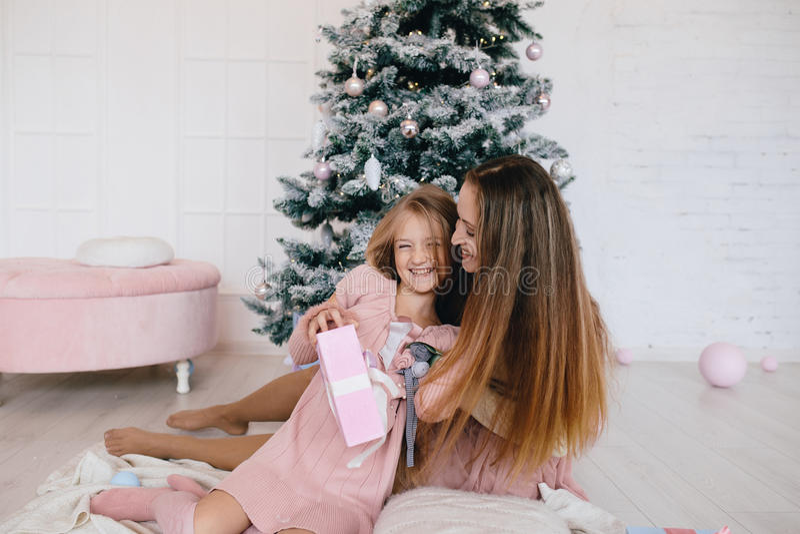 Moder och dotter som kramar den hemmastadda near julgranen kvinna och flicka med en julklapp arkivfoto
