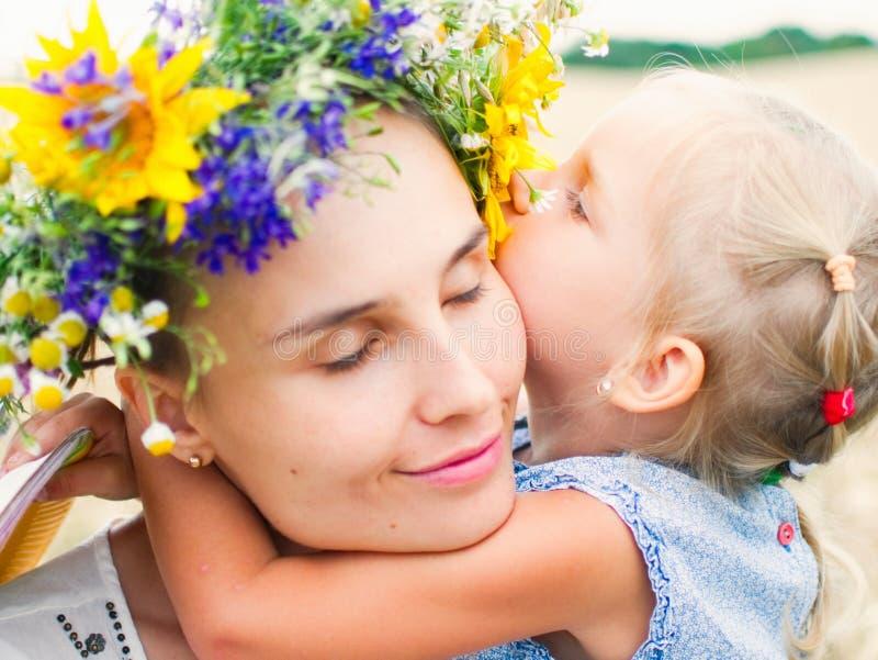 Moder och dotter som kramar förälskat spela i fältet royaltyfri foto