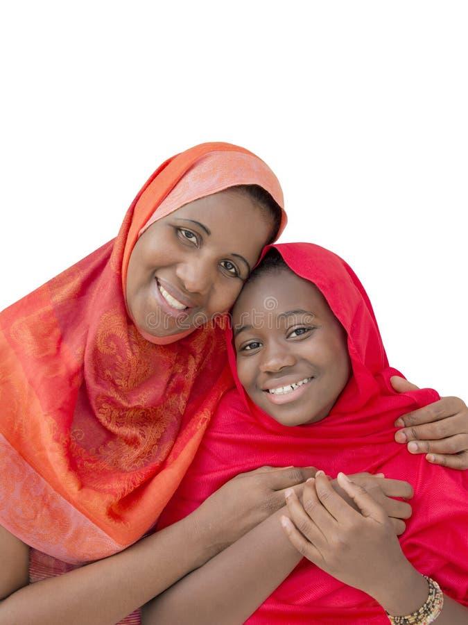 Moder och dotter som kramar sig och ler, isolerat royaltyfria foton