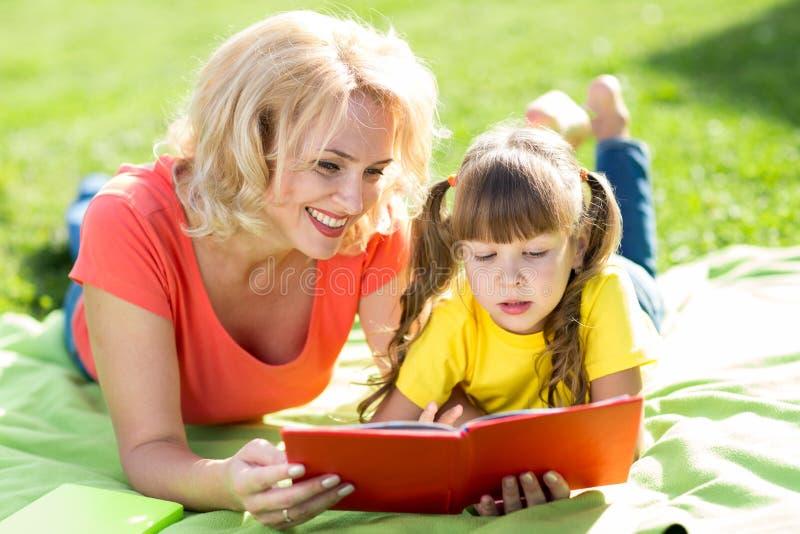 Moder och dotter som läser en bok på parkera royaltyfria foton