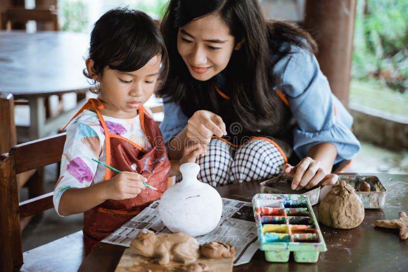 moder och dotter som m?lar den keramiska krukan arkivbild