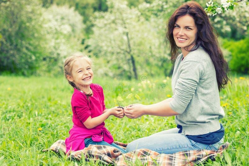 Moder och dotter som rymmer den lilla gröna växten i händer arkivfoto