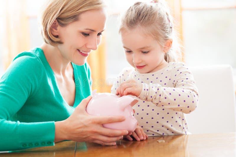 Moder och dotter som sätter mynt in i den piggy gruppen arkivfoton